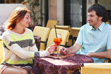 Couple at cafe table, outdoors. Italy, Europe