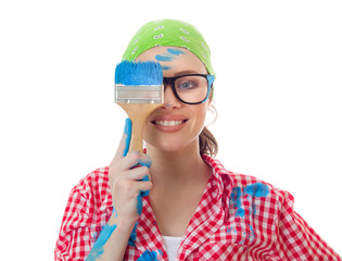 Playful woman holding paint brush over her eye