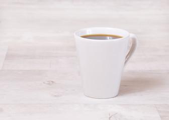 Kaffeetasse auf hellem Holztisch