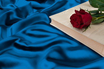Book with a rose on top of an silk background