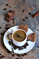 Cup of coffee with heart-shaped chocolate truffles.