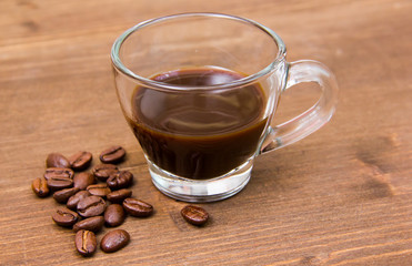 Cup of coffee and coffee beans on wooden table close up view