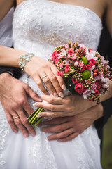 The couple cuddling and holding bridal bouquet.