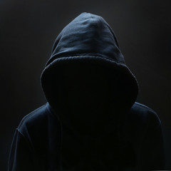Unrecognizable person wearing hood against black background
