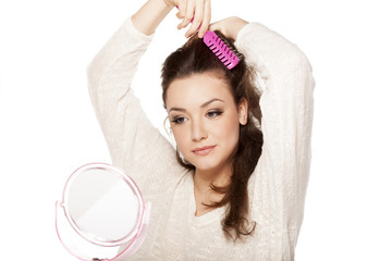 Calm young woman comb her hair