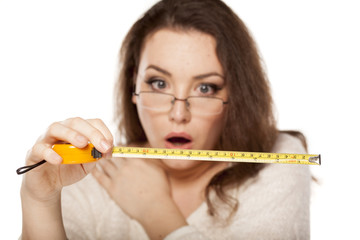 young woman is shocked by the size shown on the measuring tape