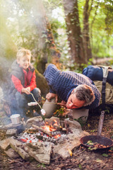 father and his son roasting marshmallows on a campfire