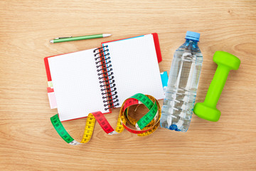 Dumbells, tape measure, water bottle and notepad for copy space