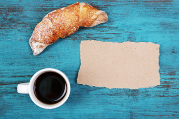 Composition of coffee, fresh croissant and paper card