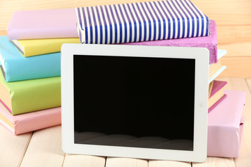 PC tablet and books on wooden table, on wooden background