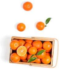 Crate of ripe tangerines with leaves, top view