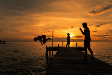 Silhouettes of kids jump into sea from pier