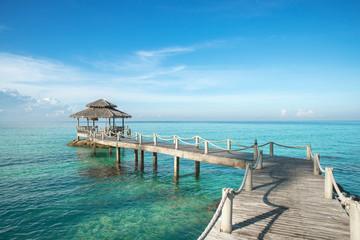 Tropical hut and wooden bridge at holiday resort - summer vacati