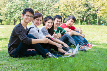 Group of student gesturing thumb up while sitting on campus