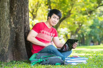 Asian student working on laptop in campus