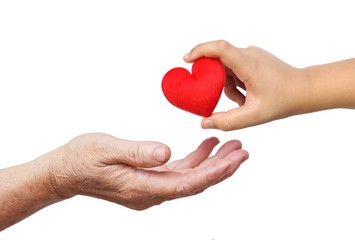 a child giving a red heart to an old female hand