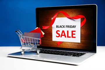 Credit cards in shopping cart and laptop, Black Friday Sale
