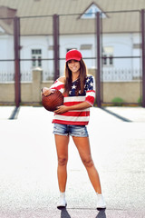 Sexy brunette woman holding basketball in hand