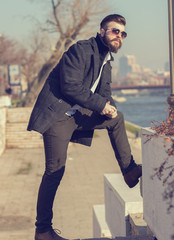 Hipster style bearded man posing on stairs