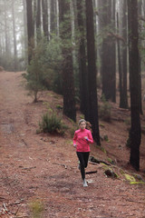 Woman running in forest woods training