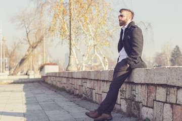 Hipster style bearded man sitting on the wall