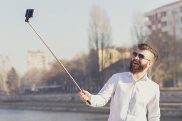Hipster style bearded man taking selfie