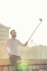 Hipster man taking selfie with selfie stick and having fun