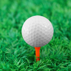 Pink golf ball on orange tee in golf course