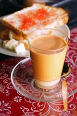 hot mlik tea with toast butter and strawberry jam