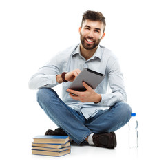 Young bearded smiling man holding a tablet with books and a bott