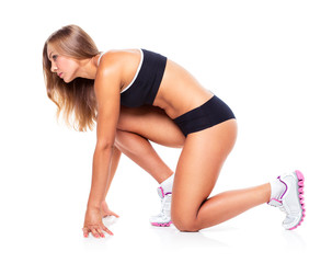 Young sports girl does exercises on a white
