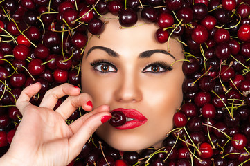 elegant beautiful woman face with cherry in hand