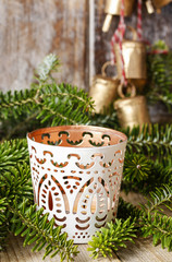 White candle holder with oriental ornaments among fir branches