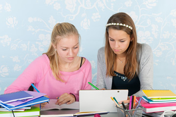 Two teen girls making homework together with digital tablet