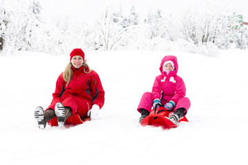 mother and her little daughter with bobs in snow