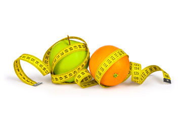 Measuring tape around the orange and green apple. Concept slim f