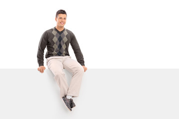 Casual young guy sitting on a blank signboard