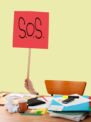 Work problem, overwork etc. SOS sign over untidy desk. Stress.