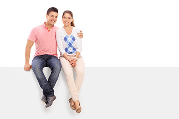 Casual couple posing seated on a blank panel