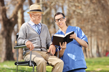 Male nurse reading a book to a senior man in a wheelchair
