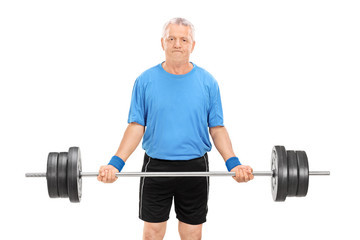 Mature man lifting a heavy barbell