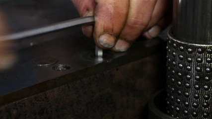 Heavy industry - Man tightening a bolt or screw using a socket