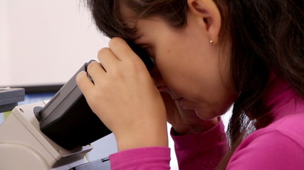 Scientist woman examining something with microscope