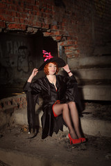 Ginger woman in black mantle on ladder in abandoned building