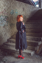 Ginger woman in black mantle in abandoned building