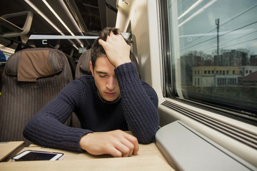 Bored tired young man traveling on a train