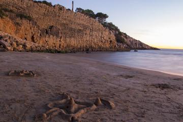 Beach at sunset wint sand castle