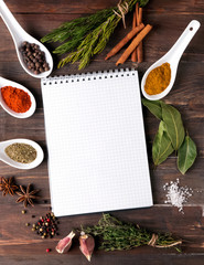 Spices, herbs and empty notebook on the table