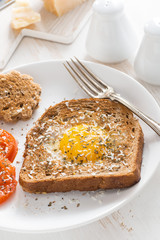 fried egg in a toast and grilled tomatoes, vertical