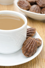 madeleine cookies and a cup of coffee with milk on a plate